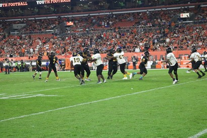 Middle school football team playing at First Energy with crowd in background