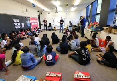 Students sitting on floor listening to adult speakers