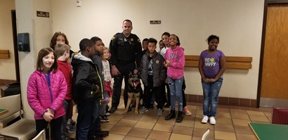 Group of students standing with police officer and K nine