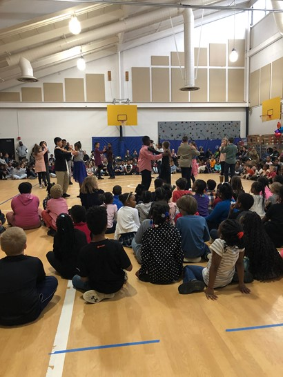 Fifth graders dancing on gym floor with crowd sitting around them