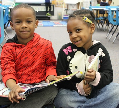 Two kindergarten students sitting with books