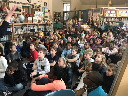 Students sitting on floor listening to author speak