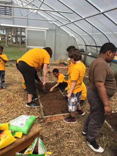 Elementary students working in garden bed