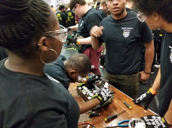 Students repair bot after one of the matches