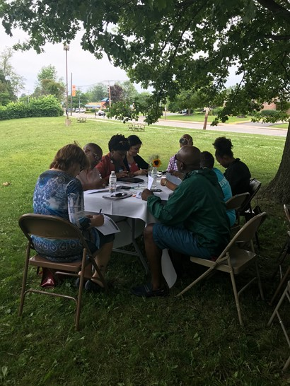 Participants sitting around table in park