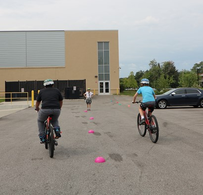 Two bicycle riders in parking lot