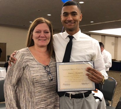 Travis with woman and holding diploma