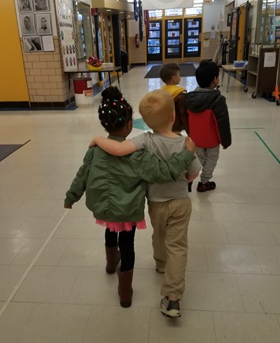 Two small children walking with arms around each other