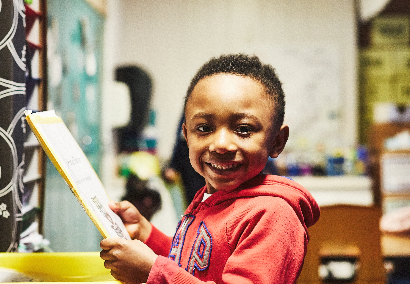 boy holding folder and smiling