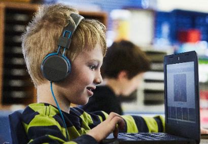 boy working on computer with headphones