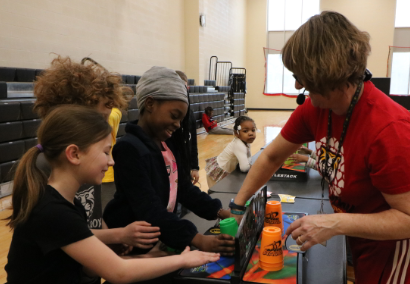 students and teacher playing cup stacking game