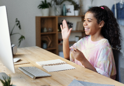 child at table with computer