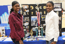 two girls in front of poster and trophy