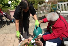 Student and older woman watering plant