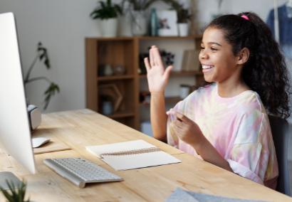girl raising hand at computer