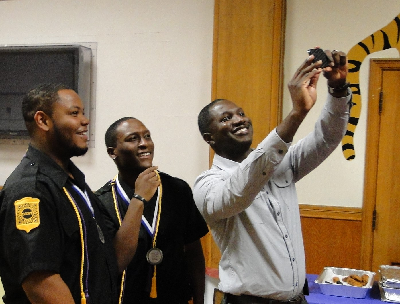 Counselor David Peake takes a selfie with two graduates.