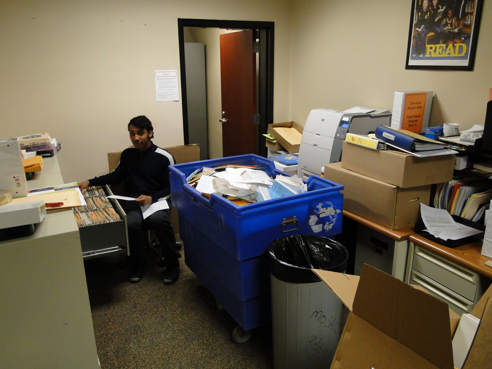 Student volunteer helps recycle outdated files.
