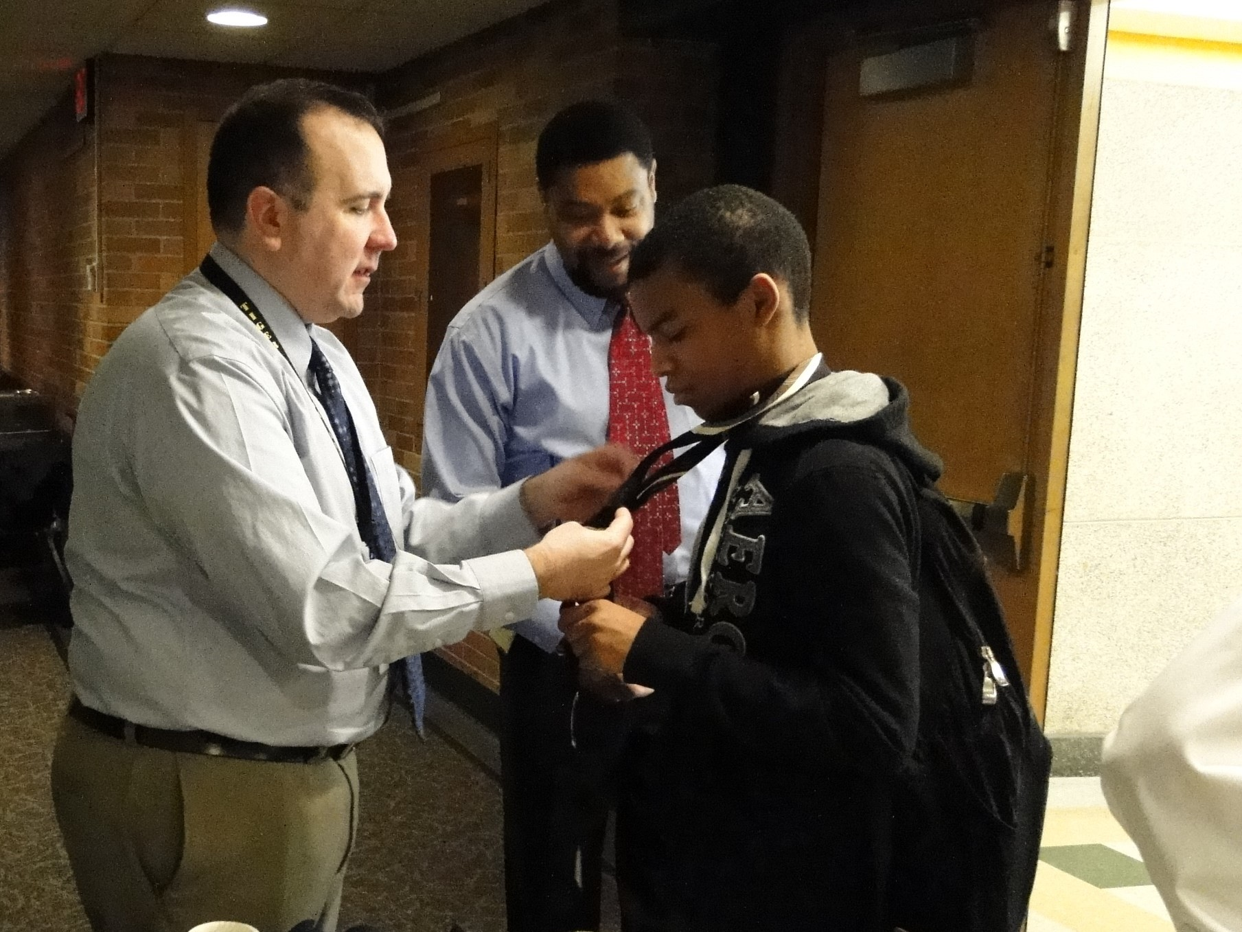 Administrator Bob Swaggard helps a student with his tie.
