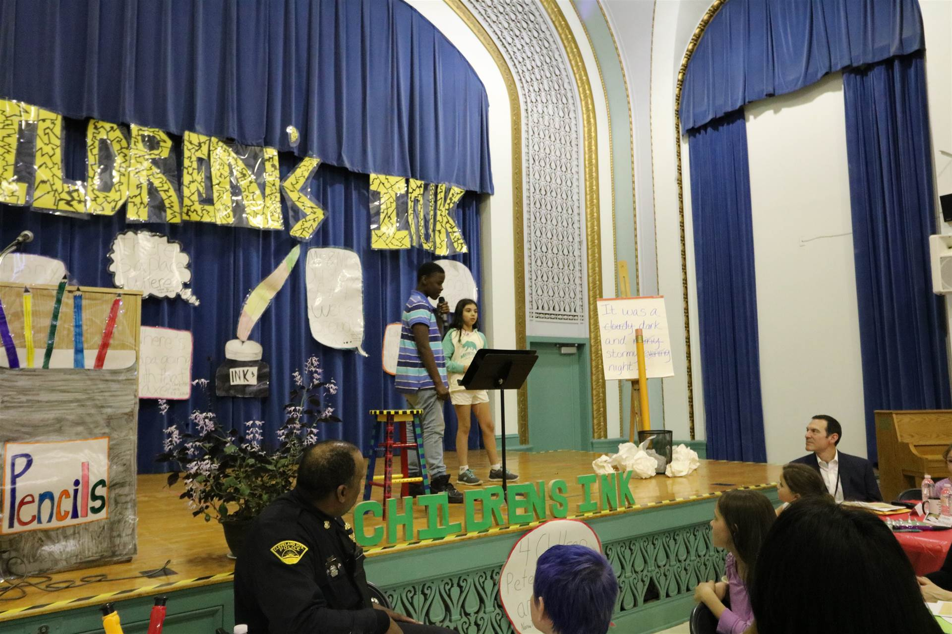 Community guests read students' writing on stage at Children's Ink