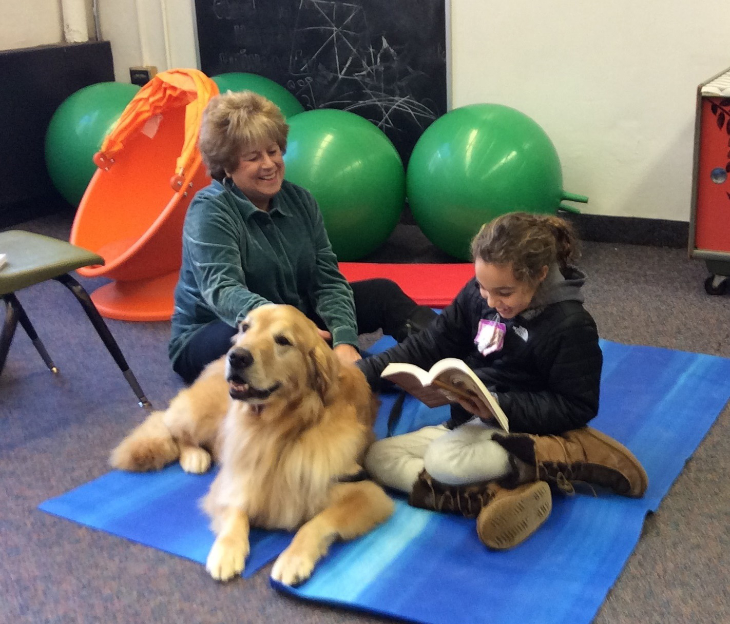 Roxboro student reading MASTERPIECE to Duke, the Therapy Dog.