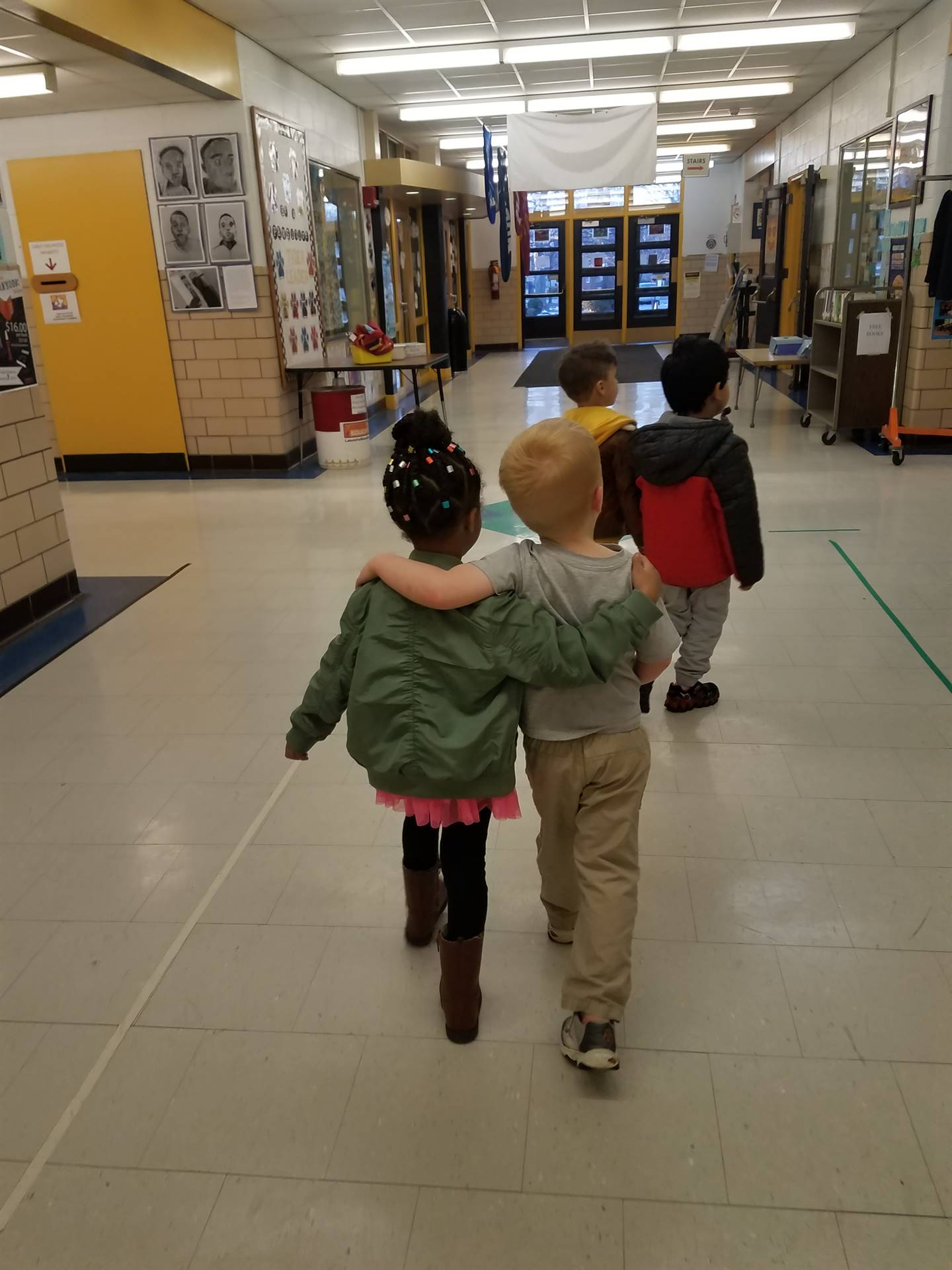 Two students walking down hall with arms around each others' shoulders