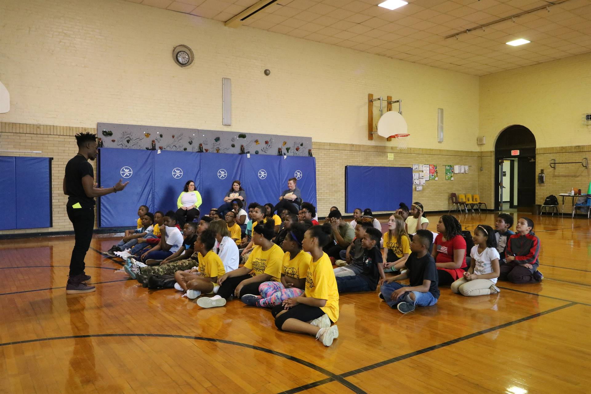 Motivational speaker talks to kids sitting on floor in Oxford gym