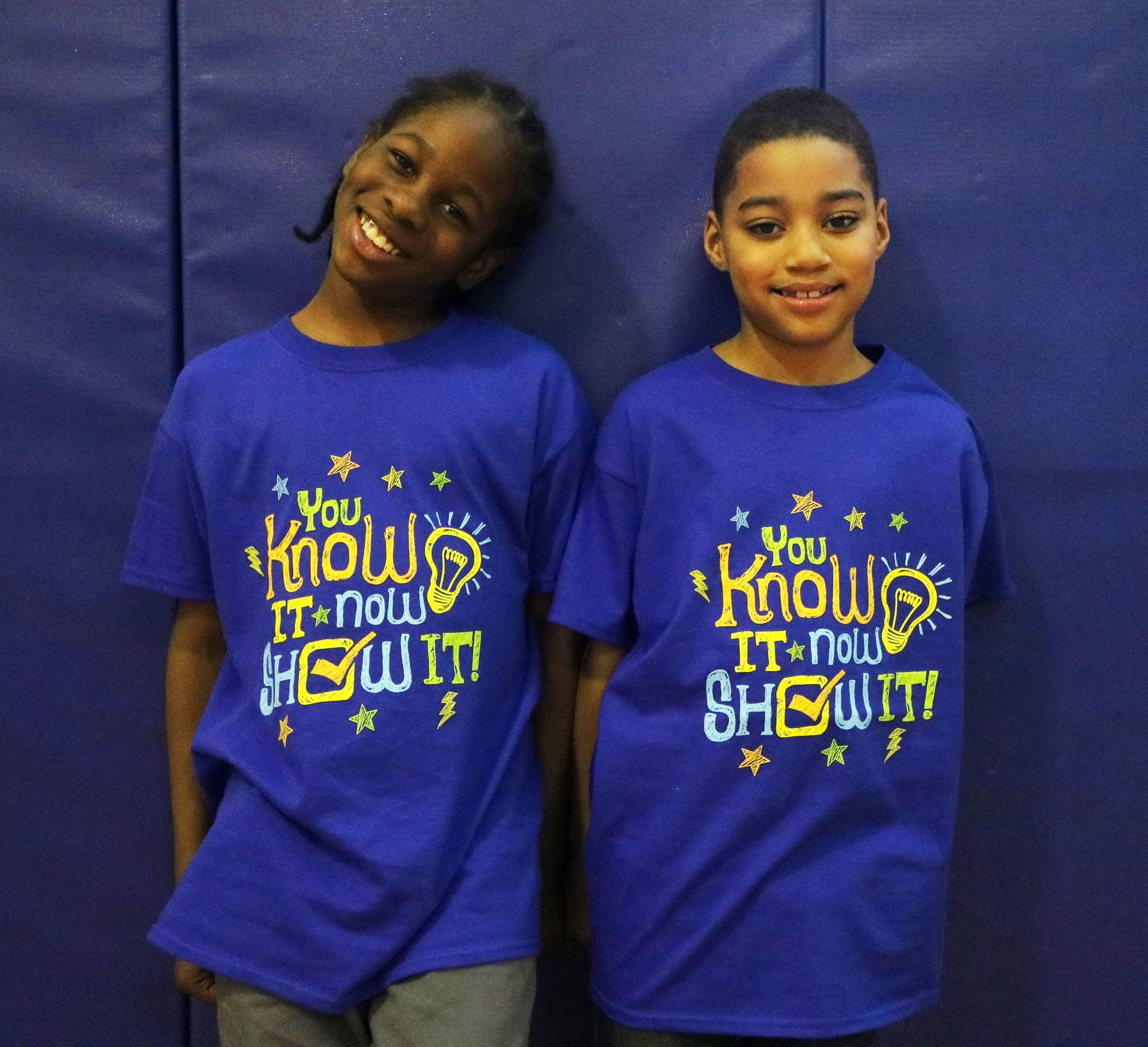 Two students with blue shirts that say You Know It Now Show It